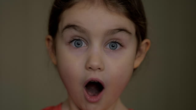 girl looks and is surprised and happy to receive a surprise. portrait little girl with blue eyes looking at camera. closeup. portrait of young child surprised and shocked . close up. - sorpresa video stock e b–roll