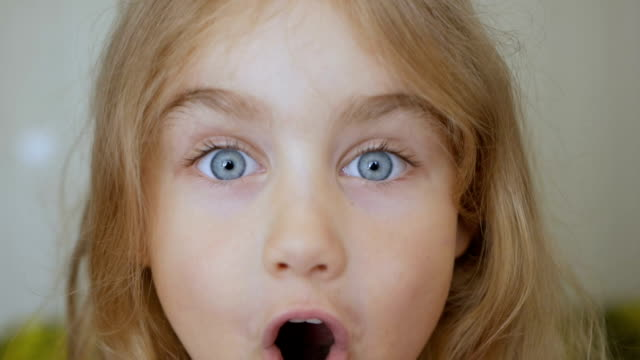 girl looks and is surprised and happy to receive a surprise. portrait little young girl with blue eyes looking at camera. closeup - sorpresa video stock e b–roll