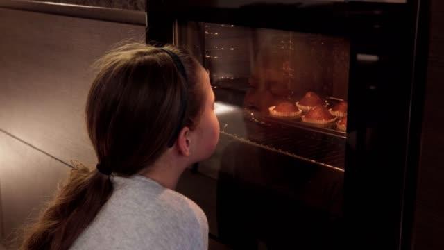 vidéos et rushes de jeune fille ressemble au four dans cuisine et attend cuire cookies - four