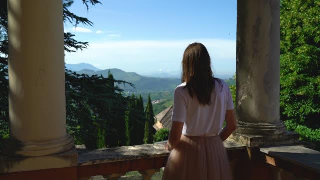 girl looks from a balcony in an old villa - вилла стоковые видео и кадры b-roll