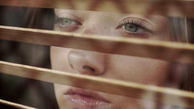 girl looks through blinds - store filmów i materiałów b-roll