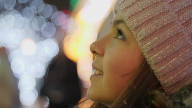 a girl looks up at a christmas tree while standing in the square - christmas lights стоковые видео и кадры b-roll