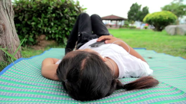 Girl lying and listen to music from smartphone,Dolly shot video