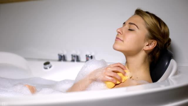 お風呂に横たわる女の子、スポンジで体を洗う、毎日の美容手順、新鮮さ - 体 洗う点の映像素材/bロール