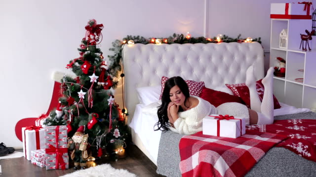 Girl lying on bed in morning with a Christmas gift video