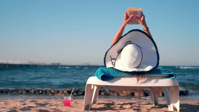 Girl lying on the beach and reading a book Girl lying on the beach, holding a hat and reading a book. Waves in the background lying down stock videos & royalty-free footage