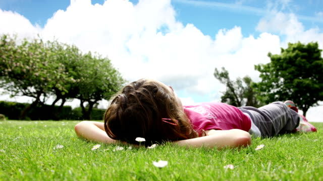 dolly: dziewczyna leżeć na trawie - leżeć filmów i materiałów b-roll