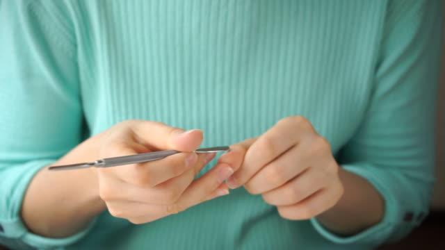 girl makes herself manicure with cuticle pusher - giuntura umana video stock e b–roll