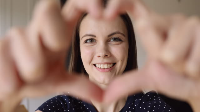 Girl makes with fingers heart looking at camera feels happy
