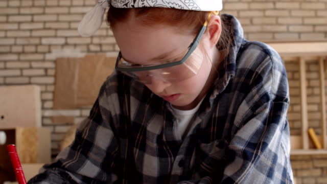 Girl Making Blueprint in Workshop