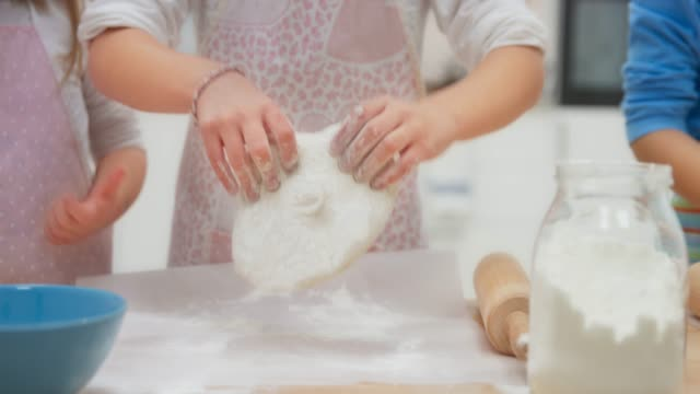 Girl making pizza dough with friends