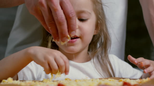 Girl Making Pizza Together with Father Close up shot of cute little girl of primary school age sprinkling grated cheese on pizza when cooking together with father cheese stock videos & royalty-free footage