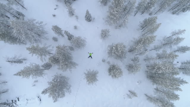 AERIAL Girl making snow angles in fresh snow on snowy mountain during the winter video