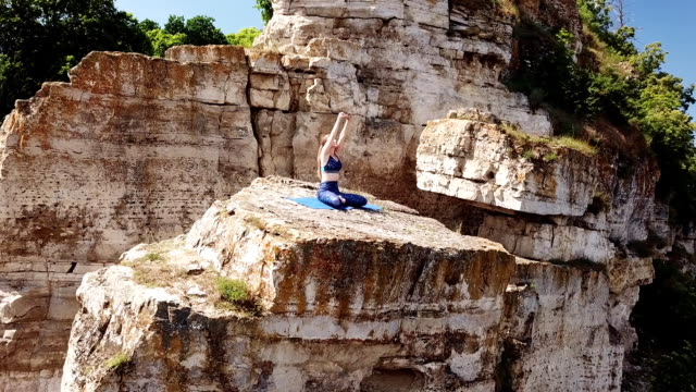 Girl making yoga pose on mountain. Aerial view on beautiful nature and crags. Yoga in the mountains,sunny day, aerial shoot of a beautiful girl on the crag. 天の川 stock videos & royalty-free footage
