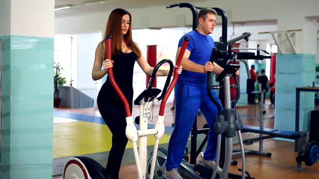 Girl man on simulator ellipsoid involved trainer  sports with video