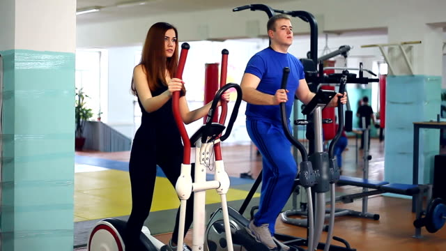Girl man on simulator ellipsoid sports involved with trainer video