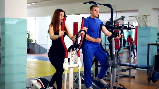 Girl man on simulator trainer sports ellipsoid involved video