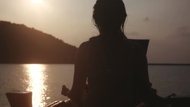 Girl meditates sits in pose of lotos on boat in the sea while has vacation during amazing sunset. 1920x1080 Girl practice lotos pose on boat in the sea while has vacation during amazing sunset. 1920x1080, hd physical position stock videos & royalty-free footage
