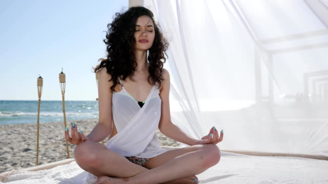 girl meditation, in bungalow, female with curls, on background sea and sand, wind develops hair and white cloth, on tropical islands - capelli ricci video stock e b–roll
