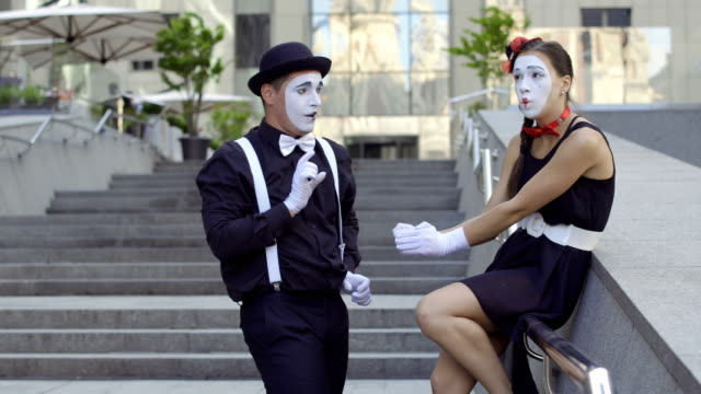 Girl mime holding heavy bouquet of flowers from her boyfriend Two funny mimes play a scene at the staircase near office center. Girl and guy gesticulates their facial expressions and hands. Young amateurs earn money showing people small funny scenes at urban streets. greasepaint stock videos & royalty-free footage