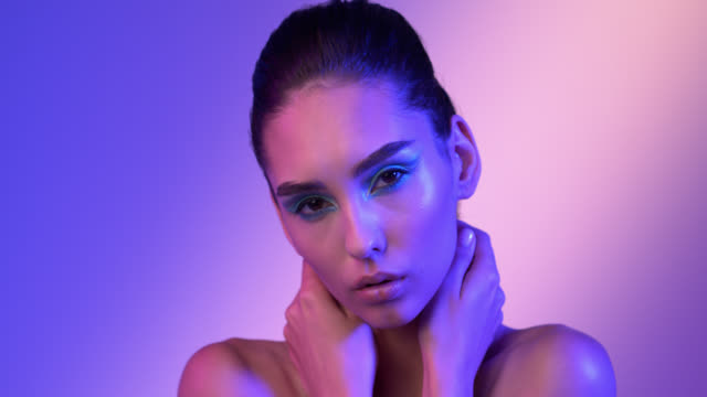 Girl model hugs herself with her hands behind her neck and looks at the camera, under pink-purple lighting. Make-up.