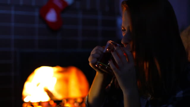 Girl near the fireplace drinking tea video