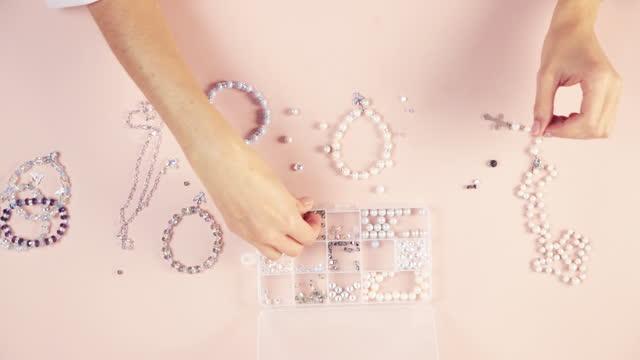 女の子の針の女性はブレスレット、手作りのマスターを作ります。クローズアップ、ブシン。 - 結ぶ点の映像素材/bロール