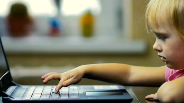 Girl of three years slowly prints text on the laptop keyboard at home in the background of the window video