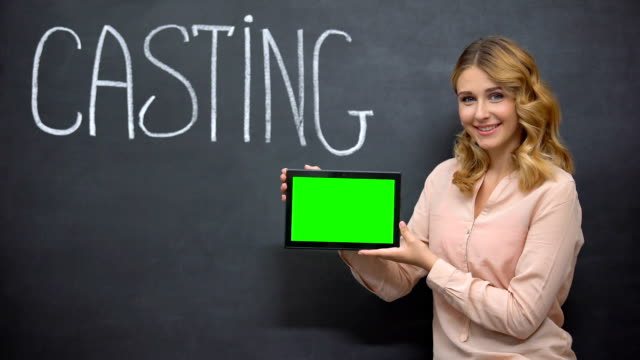 Girl offering online registration for casting, holding tablet with green screen