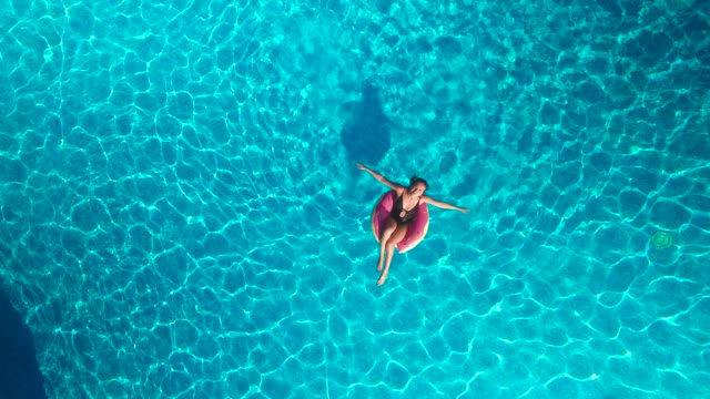 vídeos de stock e filmes b-roll de girl on a circle swimming in the pool - jump pool, swimmer