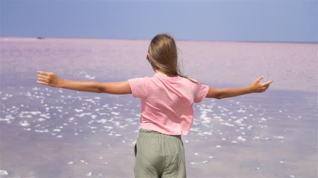 vidéos et rushes de fille sur un lac de sel rose sur une journée ensoleillée d'été. - lac salé