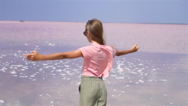 vidéos et rushes de fille sur un lac rose de sel sur une jour née ensoleillée d'été - lac salé