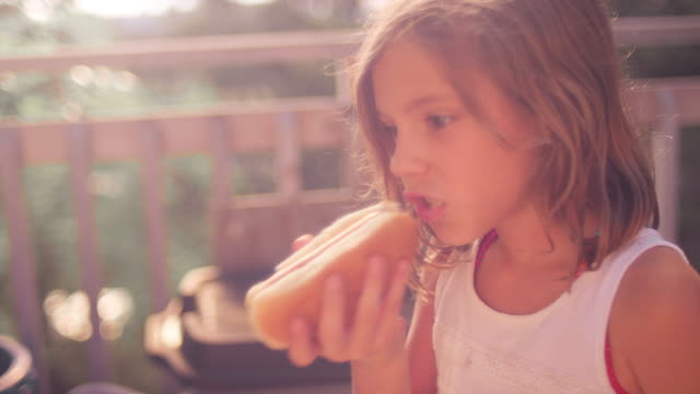 vídeos de stock, filmes e b-roll de uma garota em uma varanda comer um cachorro-quente - cachorro quente