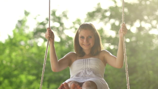 Girl on a rope swing smiling at the camera video