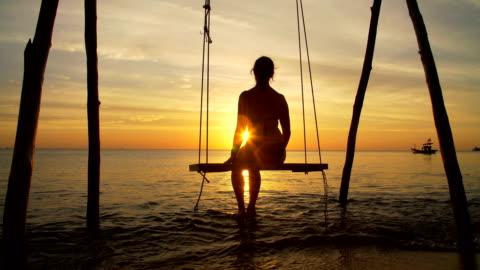 ragazza su un'altalena in riva al mare al tramonto - isola video stock e b–roll