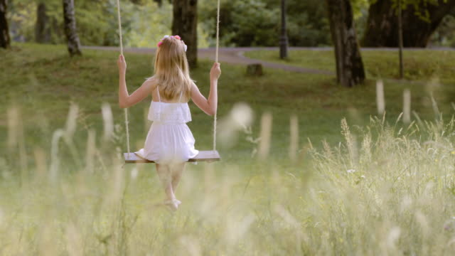 SLO MO DS Girl on a swing in nature video