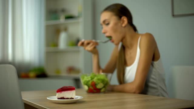 Chica dieta prefiere la torta en vez de ensalada, tentación, estilo de vida poco saludable - vídeo