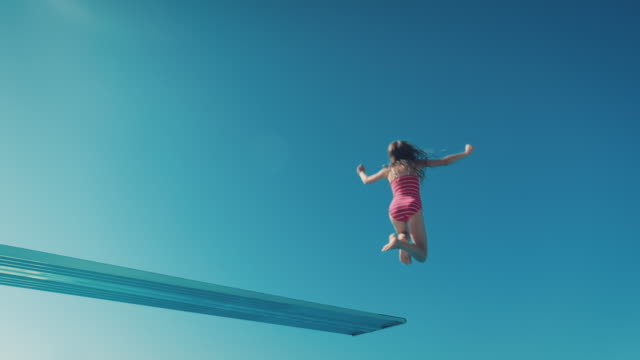 Girl on diving board A young girl climbs up a diving platform. She takes courage to jump into the pool. Its a beautiful summer day. bolos stock videos & royalty-free footage