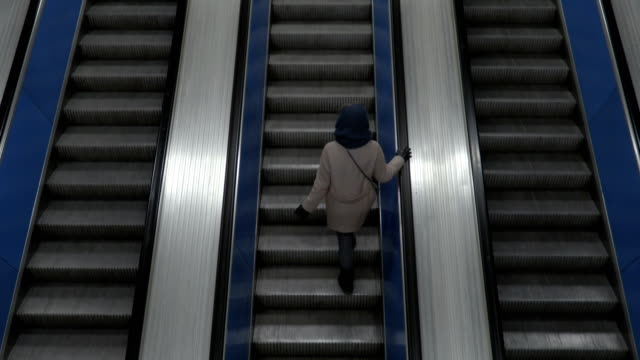 girl on escalator from top view - escalator video stock e b–roll