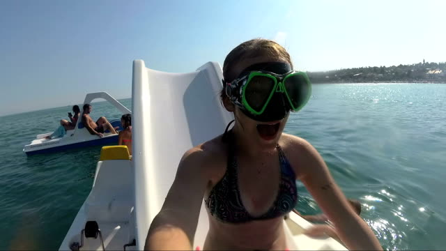 girl on pedal boat pulls off the hill into the sea, view from water video