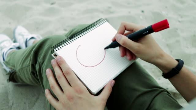 mädchen am strand in der abend zieht in ein notebook mit rotem filzstift smiley, nahaufnahme - smiley stock-videos und b-roll-filmmaterial