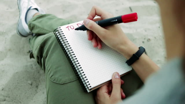 """girl on the beach writing in a notebook with red felt-tip pen task """"be happy"""". concept, outdoors, evening. - to do list video stock e b–roll"""