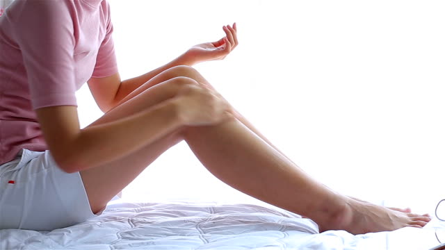 Girl on the bed to put a cream on legs. beautiful woman skin care video