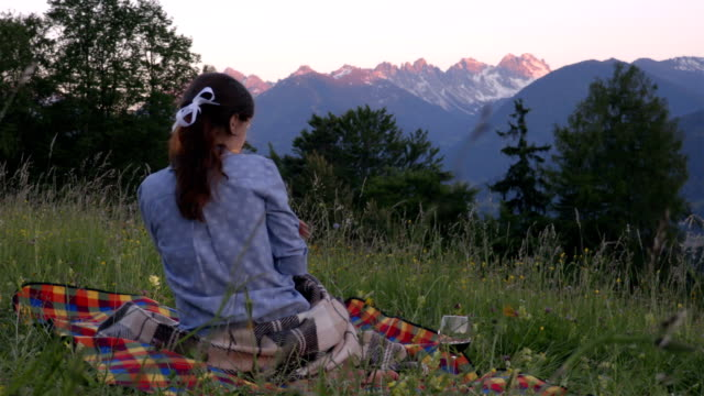 Girl on the picnic in the alps wrapped in a blanket video