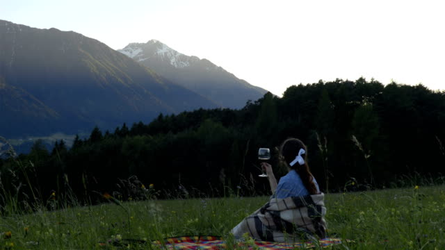 Girl on the picnic with the glass of wine in the alps sunset time video