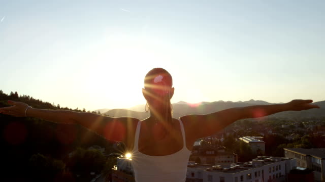 CLOSE UP: Girl on top of skyscraper standing on the edge raising hands in air video