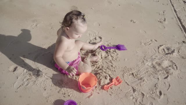 vídeos de stock e filmes b-roll de girl one year plays in the sand on the beach. concept: children, childhood, summer, freedom, kids, baby. 4k - bebé praia