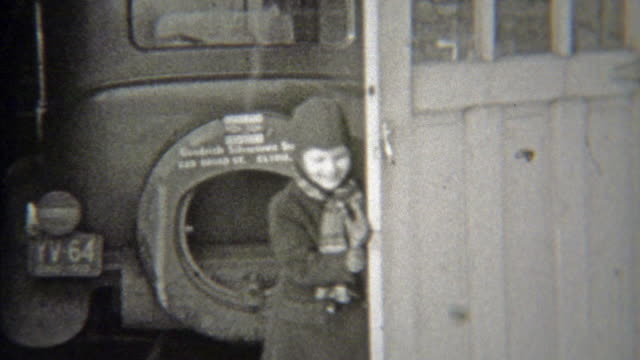 1938: Girl opening garage to get winter sleigh out for play. video