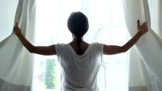 Girl opens the curtains in the morning, slow motion video