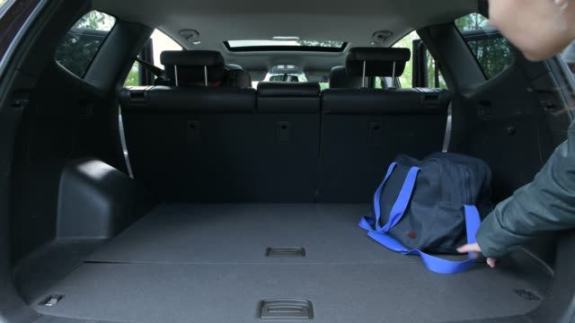 girl opens trunk of suv, picks up the bags from there and puts the bags back
